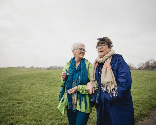 Two senior female friends walking in the park together, laughing and smiling.