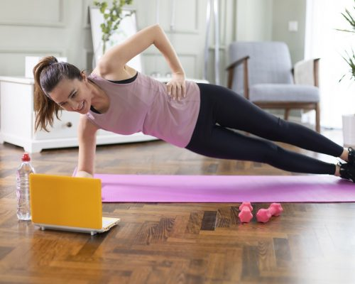 Young woman exercising at home in a living room. Video lesson. She is repeating exercises while watching online workout session.