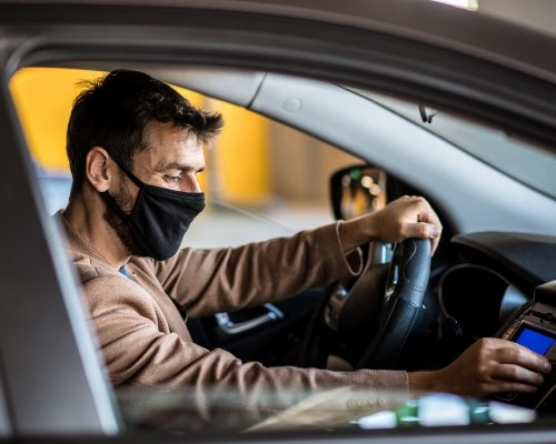 A young man drives a car with a mask on his face and adjusts the music in the car, life during a pandemic caused by a virus