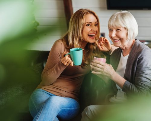 Happy senior mother with adult daughter sitting on couch and holding cups with coffee or tea at home. Togetherness concept