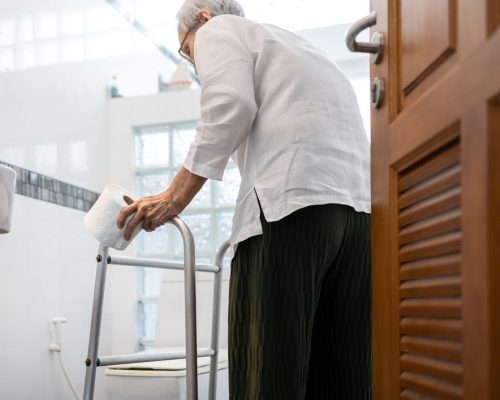 Senior woman with diarrhea holding tissue roll near a toilet bowl,elderly have abdominal pain,stomach ache,constipation,sick people use walker to walk to the bathroom,belly diarrhea,irritable bowel