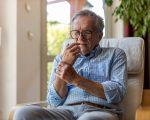 Senior man with arthritis rubbing hands