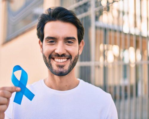 Young hispanic man smiling happy holding blue ribbon at the city.
