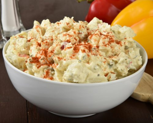 A bowl of potato salad on a rustic wooden table
