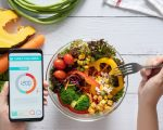 Calories counting , diet , food control and weight loss concept. Calorie counter application on smartphone screen at dining table with salad, fruit juice, bread and fresh vegetable. healthy eating