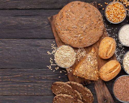 Healthy lifestyle. Wholegrain bread with gluten free grains on wooden background, copy space