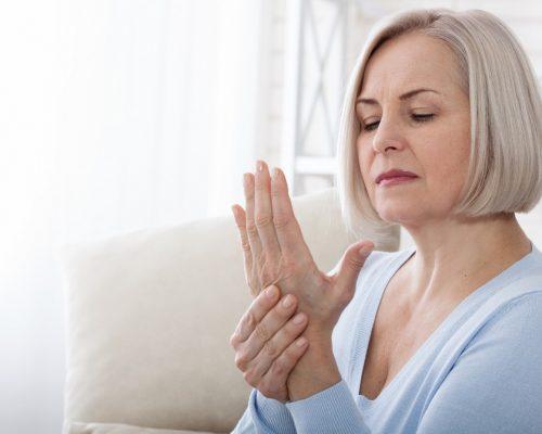 Woman massaging her arthritic hand and wrist closeup