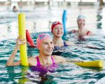 Smiling mature female in swimwear and two more active women listening to trainer advice during gymnastics in water