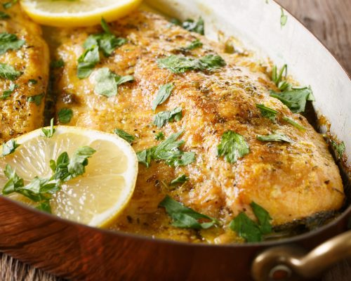 Delicious food: trout fish with garlic lemon butter sauce, parsley close-up in a copper frying pan on the table. horizontal