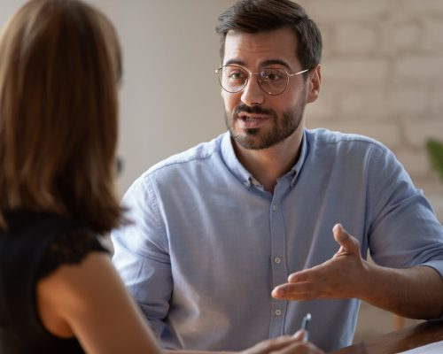 Caucasian male applicant answers on questions to HR female manager during job interview in office. Meeting process, negotiations communications between business parties, solutions and opinion concept