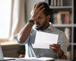 Stressed african businessman sit at desk hold paper letter reading bad awful negative news got fired from work. Dismissal notice, financial problems debt notification from bank, unpaid invoice concept