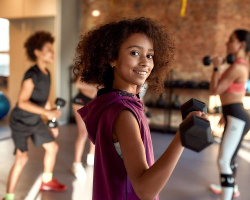 African american girl smiling at camera while exercising using dumbbell in gym together with female trainer and other kids. Sport, physical education concept. Horizontal shot. Selective focus