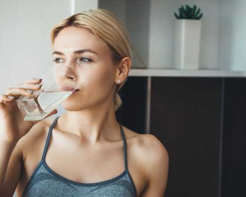Young fitness lady drinking water after yoga exercises wearing sportswear at home in the kitchen