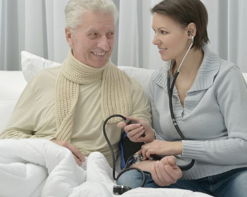 ill Senior man and caring daughter at home measuring blood pressure