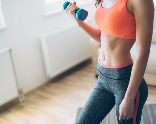 Young attractive sportswoman doing fitness exercises at home