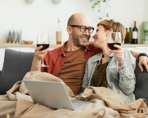 Happy mature couple sitting on sofa with glasses of red wine using laptop computer and laughing