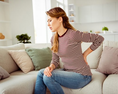 Close up side profile photo beautiful she her lady arms hands hold back spine suffering terrible pain wear jeans denim striped pullover clothes bright comfort flat house living room indoors.