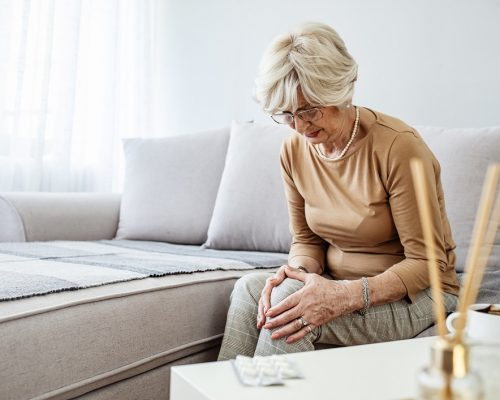 Old age, health problem and people concept - senior woman suffering from pain in leg at home. Elderly woman suffering from pain in knee at home.