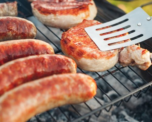 Toasty yummy frankfurters and chicken thighs roasted on barbecue grill