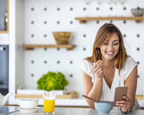 Beautiful young woman having breakfast in the kitchen. Beautiful cute smiling woman is using smart phone on the kitchen at home. Woman Eating Breakfast Whilst Using Mobile Phone
