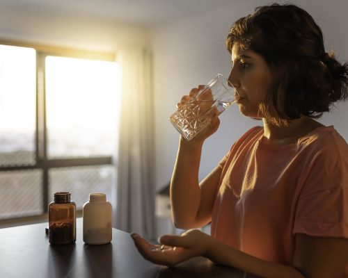 Shot of a young woman taking supplements at home