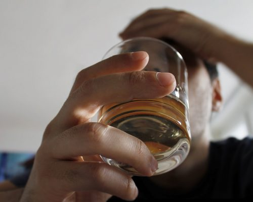 Young guy holding glass of alcohol.