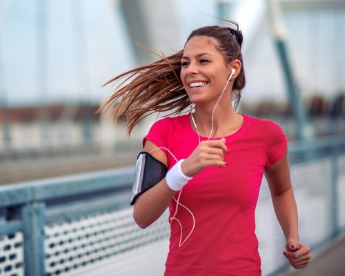 Positive beautiful female runner exercising outdoors on sunny summer morning.