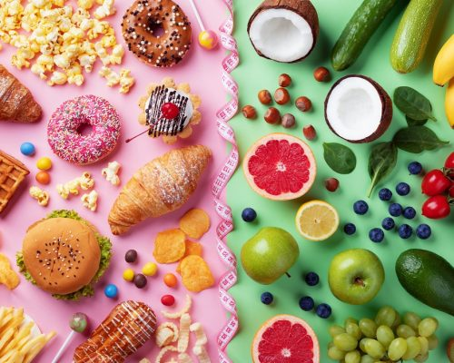 Healthy and unhealthy food background from fruits and vegetables vs fast food, sweets and pastry top view. Diet and detox against calorie and overweight lifestyle concept separated with measuring tape.