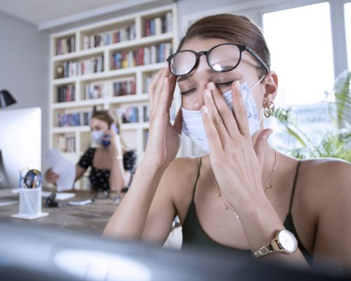 two woman working with protective face mask at office