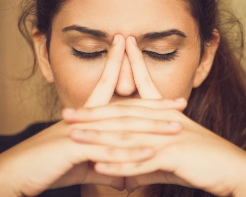 Close-up of face of tired young Caucasian woman rubbing nose. Businesswoman suffering stress or depression
