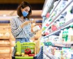 Young woman in disposable face mask taking dairy products from shelf in the supermarket, holding bottle and smartphone, scanning bar code on product through mobile phone, walking with trolley cart