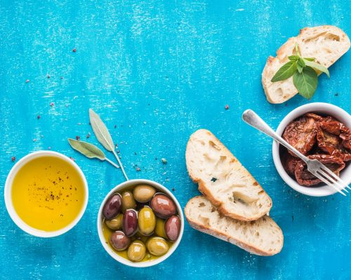 Mediterranean snacks set. Olives, oil, sun-dried tomatoes, herbs and sliced ciabatta bread on over blue painted background, top view, copy space