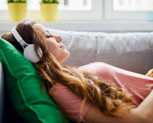 Portrait of a beautiful young woman lying on sofa with headphones on and closed eyes, relaxing