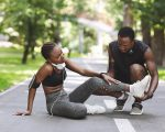 Caring Black Man Massaging Injured Leg Of Girlfriend After Running Together Outdoors, Free Space