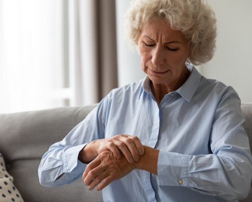 Unhappy senior old hoary woman touching wrist joint, suffering from injured hand. Frustrated stressed middle aged mature female retiree having painful feelings in bones, arthritis osteoporosis concept