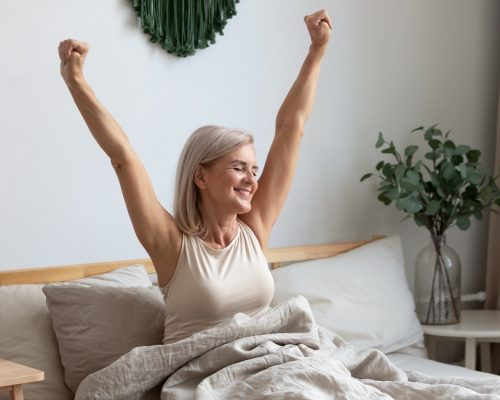 Active happy mature female wake up from good healthy sleep stretching sitting in bed at home, smiling positive senior woman awaken in comfortable bedroom feel optimistic welcome new day