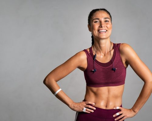 Portrait of beautiful fitness woman smiling and looking at camera isolated on grey background. Laughing mid woman in sportswear wearing wireless headphones and relaxing after training at gym. Happy fit girl excited about workout on gray wall with copy space: wellness and wellbeing concept.