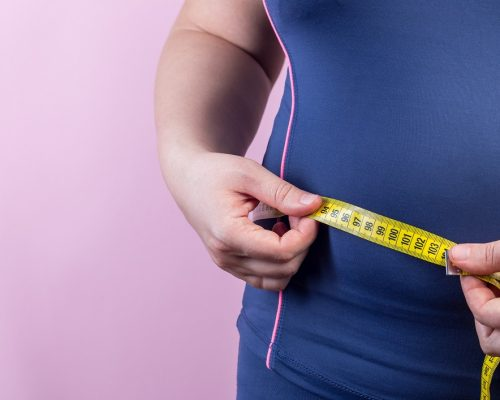 Overweight woman with measuring tape on a waistline, closeup