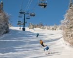 view of skiers climb the ski lift up the hill with snow covered mountains. Ski chairlift climb above the ski slope