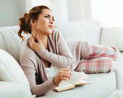 Young woman having neckache while lying down on sofa and reading book in the living room.