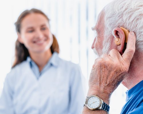 Focused picture of an elderly male patient with hearing aid side view with blurred woman doctor in the background
