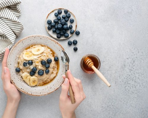 Oatmeal porridge bowl with blueberries, banana, coconut and honey in female hands. Top view copy space for text, grey concrete background. Concept of dieting, clean eating
