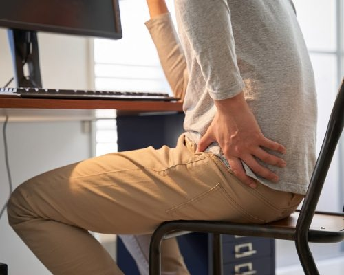 Japanese male businessman who suffers back pain from working from home